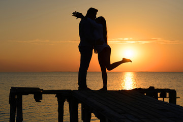 Silhouette of a kissing guy and a girl on a bridge by the ocean at sunset. Honey month (love and romance)