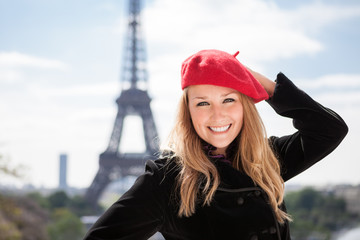 Young woman in red hat portrait in front of the Eiffel Tower in Paris