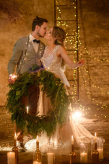Stylish hipster wedding couple in romantic loft decorations at night