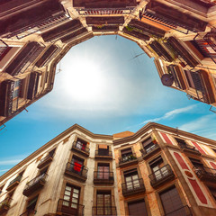 Wall Mural - Backstreet with unusual curved houses, bottom-up view with sun in a blue sky, Carrer de Milans in Barcelona, Catalonia, Spain
