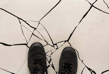 Black shoes on cracked floor copy space