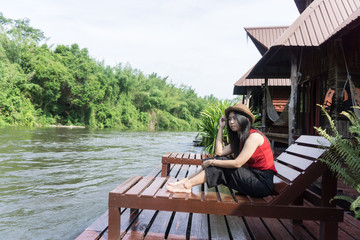 Happy Asian girl red shirt and brown hat on the river in nature background, Relax time on holiday concept travel., Thailand river kwai and typical landscape kanchanaburi., with copy space for text