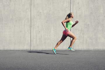 Läuferin vor Beton auf Aspahlt