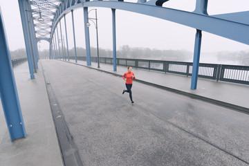 Läuferin läuft bei Nebel über eine Brücke in Magdeburg, Deutschland