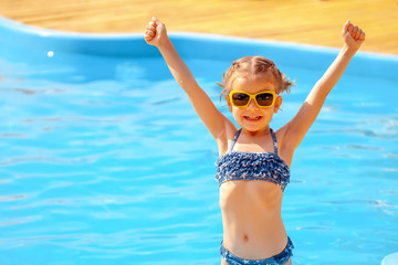 Summer vacation concept. Little cute girl in sunglasses holding hands up near a swimming pool.
