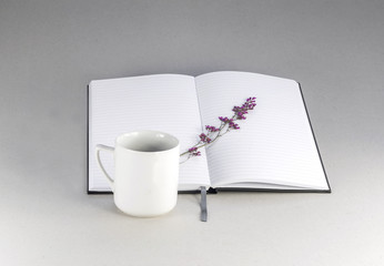 White vintage cup on the background of a note pad