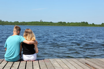 Teenagers on a lake date on a far-advanced jetty.