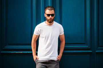 Hipster handsome male model with beard wearing white blank t-shirt with space for your logo or design in casual urban style