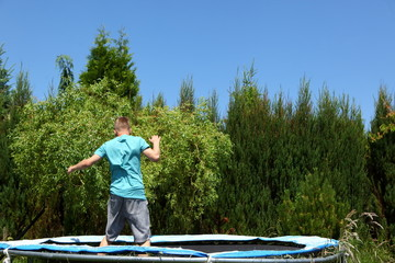 Teenager is practicing on a trampoline.
