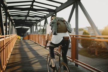Radfahrer fährt mit Singlespeed bei Sonnenuntergang durch die Stadt