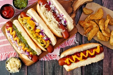 Hot dogs with assorted toppings and potato wedges, above view on a rustic wood background