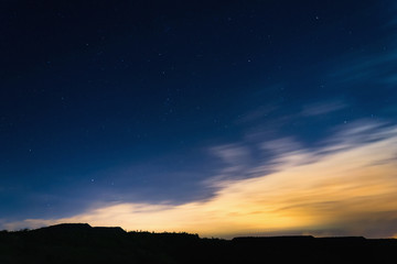 Night sky with stars next to horizon silhouette at summer