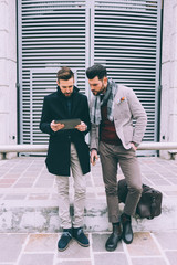 two young bearded business men outdoor using tablet