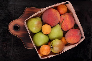 Pears, peaches and apricots in a basket on a dark background