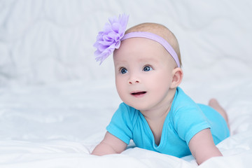 Cute baby girl in blue shirt, with bow flower on head, lying on stomach on soft blanket and looking with surprise, indoors