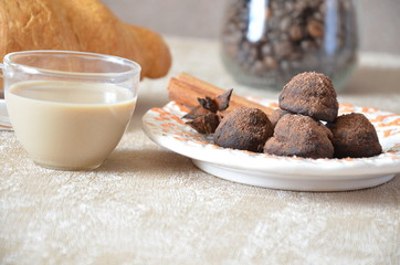 Chocolate truffles with and cinnamon. Candy, chocolate, Croissant and a cup of coffee