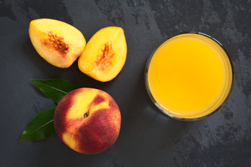 Obraz Peach juice or nectar in glass with fresh ripe peach fruit on the side, photographed overhead with natural light (Selective Focus on the juice and the top of whole fruit) - fototapety do salonu