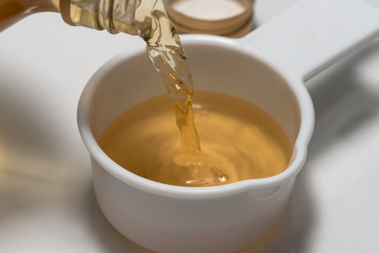 Pouring Apple Cider Vinegar into a Measuring Cup