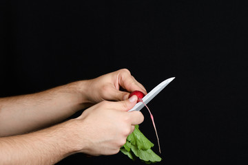 Men's hands cut of radishes on weight, isolated on black background