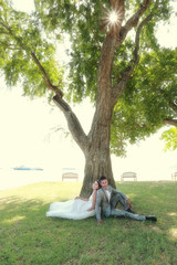 photograph of Pre wedding Asian couples Under a tree in a flower garden.