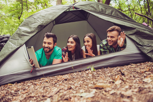 Hello from the camp vacation! Four joyful friends are waving to the camera in a tablet, lying in the tent in forest