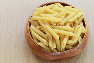 Raw Macaroni in the wooden bowl on wood background.
