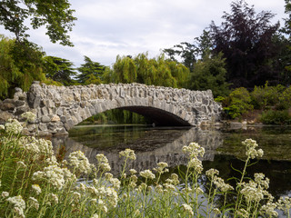 Beautiful Stone wall bridge over a river in a pretty park surrounded by nature