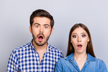 Omg! Noway! Curious shocked couple, standing in casual shirts, isolated on pure background with wonderment