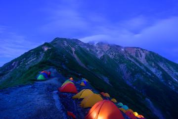 北アルプス 夜の五竜岳とテントの明かり