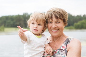 Happy grandmother with her grandchild outdoors in the summer.