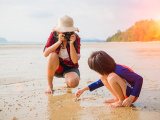 Vacation summer and travel concept. Pretty woman photographing her kid at tropical beach.