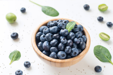 Blueberries in Wooden Bowl on white background. Fresh summer berry isolated