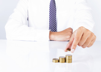 Close up of business man hand holding coins and putting on coin stack for financial ideas concept