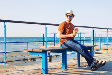Portrait of cheerful attractive bearded hipster young man drinking iced coffee or frappe on the background of the sea