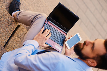 The stylish bearded male sits on a step and using laptop.