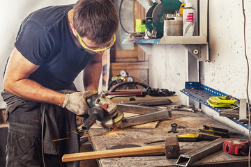 An adult man in work clothes and protective green glasses is engaged in manual labor and   grinder metal an angle grinder  on a wooden table in the workshop