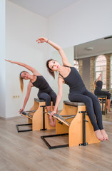 Young women exercising on pilates combo wunda pilates chair