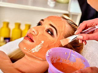 Collagen face mask. Facial skin treatment. Woman receiving cosmetic procedure in beauty salon. Bottle with moisturizing cream on background. Cosmetic masks with natural ingredients.