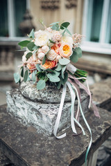 Rich wedding bouquet lies on the marble porch