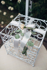 White cage decorated with green leaves and rose