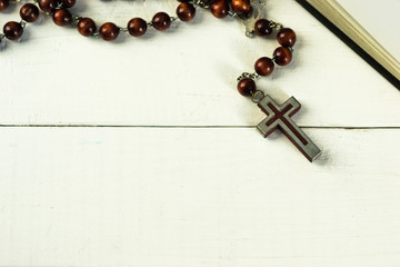 Bible and a crucifix on a white table. Beautiful background.Religion concept.