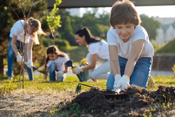 Delighted brunette kid preparing soil for usage