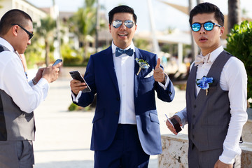 Groom and groomsmen in sunglasses pose outside