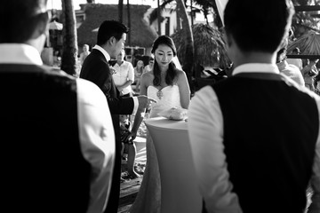 Look from behind the guests at cheerful newlyweds during the ceremony
