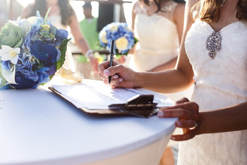 Bride signs the wedding papers