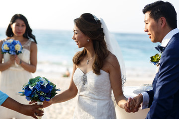 Newlyweds hold their hands together standing on the beach