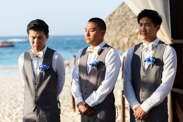 Asian groomsmen stand straight during the ceremony