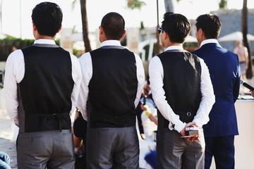 Look from behind at groomsmen standing straight behind a groom