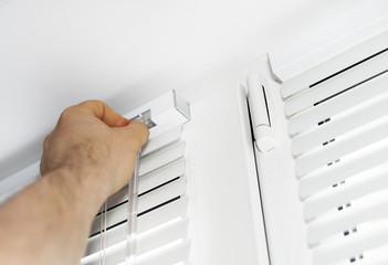 Man installing venetian blinds on windows.