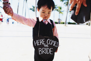 Little child holds black heart with lettering 'Here comes the bride'